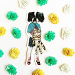 Japanese Chin illustrated vinyl sticker. Dog wearing clothes with a cat. Photograph has sticker surrounded by sequins.
