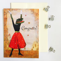 "Vintage illustration of a dressed up alligator, arms in the air, with a red polka dot skirt. Text says ""Congrats!"""