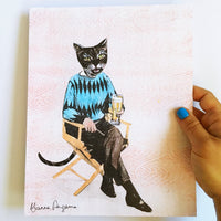 Hand holding an art print of a cat drinking a beer