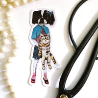 Original illustration sticker of dog and cat friends. Dressed up dog is holding a cat. Pictured with pearls and scissors.