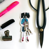 Flat lay of sticker with office supplies. Vintage clothes wearing dog holding a cat. Dog and cat friends