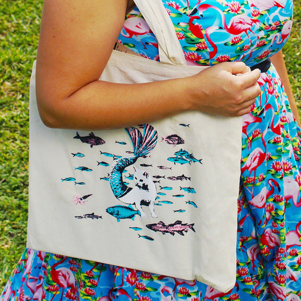 Tote Bag Over Arm. White Mermaid Cat Surrounded by Pink and Blue Fish.