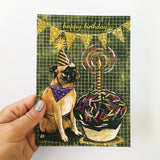 Hand holding greeting card, image of pug with huge cupcake, text says Happy Birthday