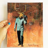 "Hand holding an 8x10"" art print. Mixed media illustration of vintage dressed buck on a brown background. Buck is wearing a blue suit."