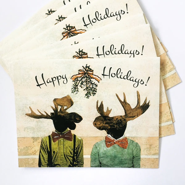 set of gay christmas cards featuring a moose couple under mistletoe text reads happy holidays