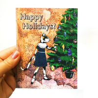 Hand holding holiday card featuring a cat putting an ornament on a Christmas tree