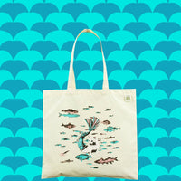 Tote bag with illustration of a swimming mermaid cat. Cat is white with a blue and pink tail. Surrounded by blue and pink fish.