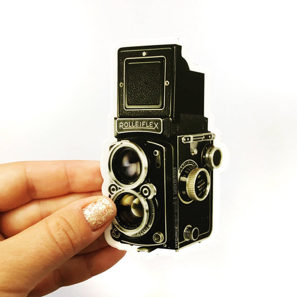 Hand holding an antique camera sticker