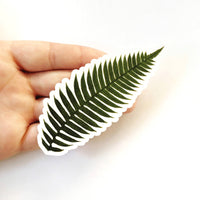Hand holding fern sticker, naturalistic fern leaf.