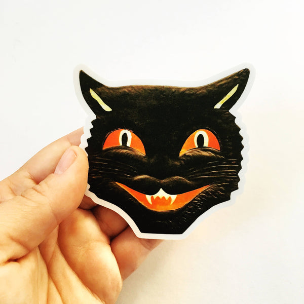 Hand holding vintage cat face sticker