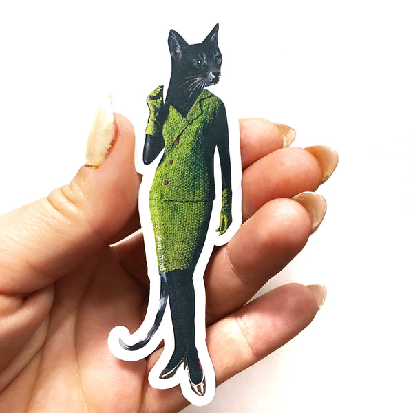 Hand holding a sticker, illustrated cat vinyl sticker; cat is wearing an avocado colored two piece dress suit