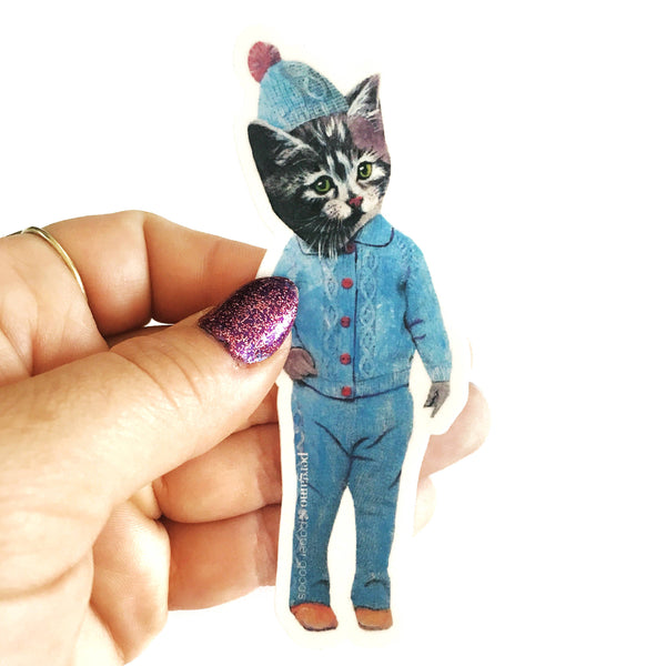 Handmade Kitten Vinyl Sticker being held. Kitten is dressed up in vintage blue pajamas with a hat.