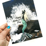 Happy Mother's Day Greeting Card being Held. Image is mixed media illustration of a mermaid cat with waves crashing behind her.