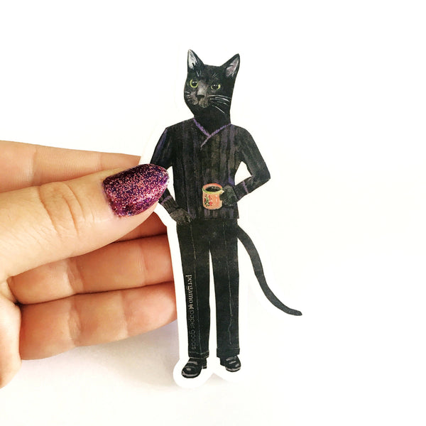 Hand holding a vinyl sticker of a black cat holding a cup of coffee