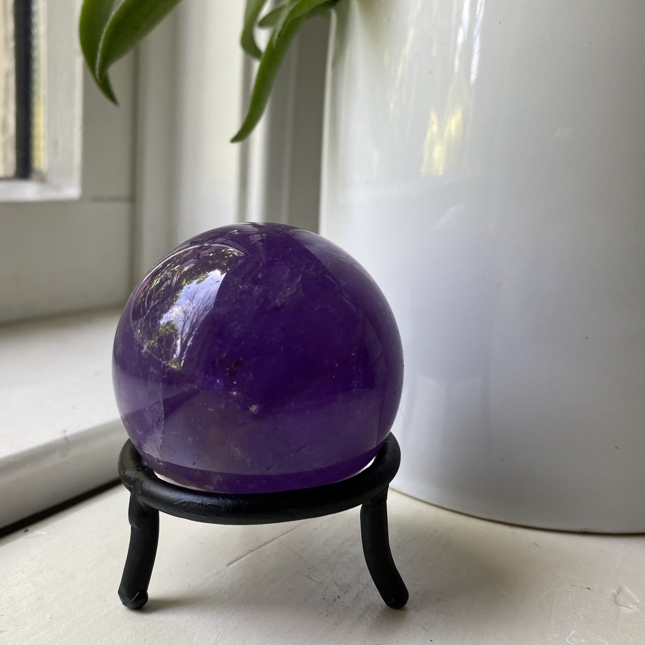 polished amethyst crystal sphere with stand
