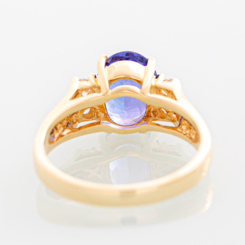 Blue Oval Tanzanite ring with diamonds in 14k yellow gold.