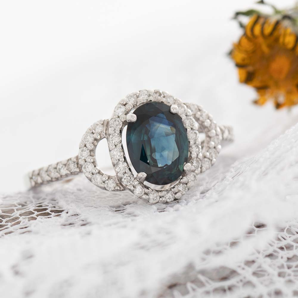 Blue Eyes electric blue sapphire with diamond halo in 14k white gold.