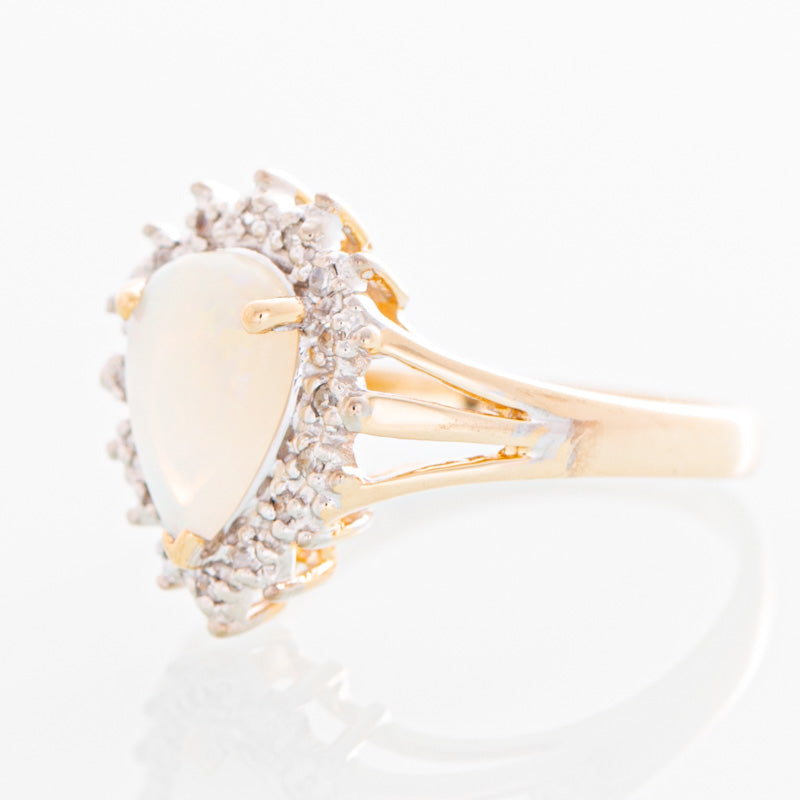 Starry pear opal ring with diamond halo in 10k gold.