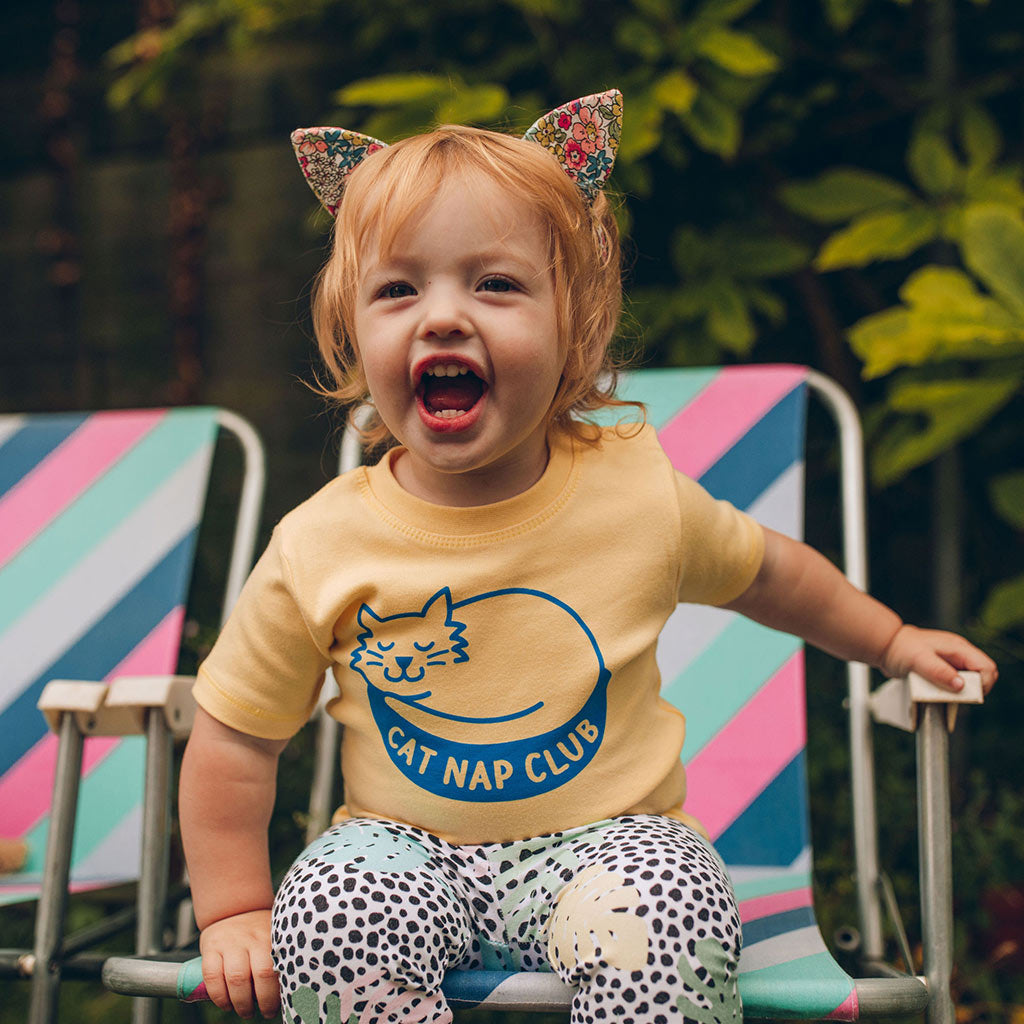 a toddler wears a t-shirt with a sleeping cat and the words 'cat nap club'. She also wears cat ears and roars at the camera, looking like she has no intention of napping...