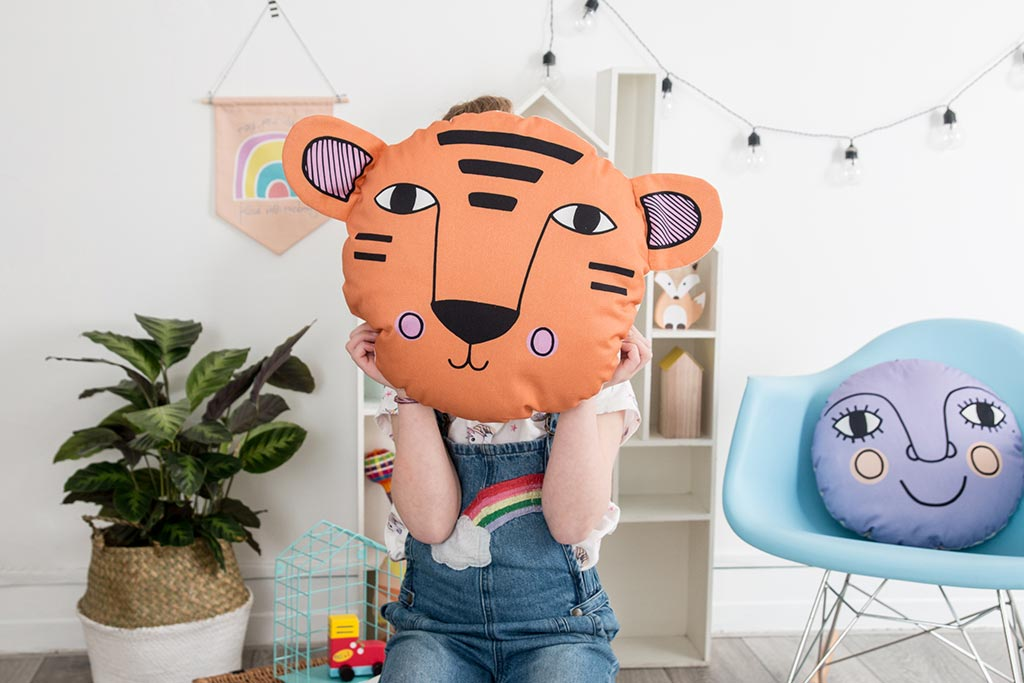 A cute tiger face cushion being held up in front of the face of a kid