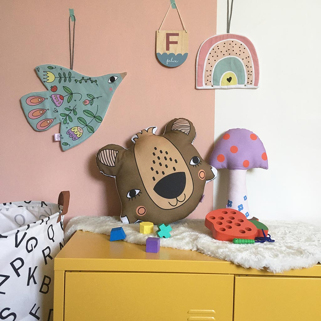 A gorgeous scandi style kids bedroom featuring a bear pillow and cute bird and rainbow wall hangings