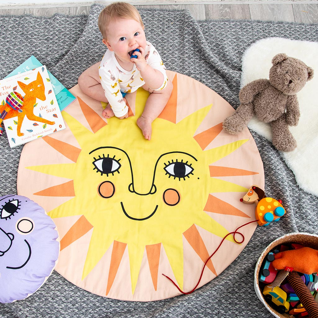 A round baby play mat with a smiley sun on it