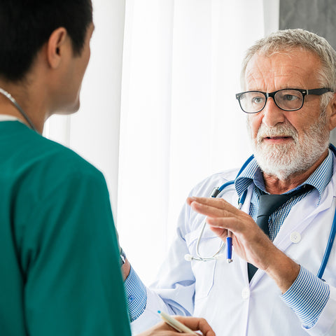 Senior male doctor working with another doctor in hospital