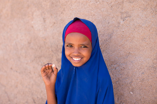 A young girl smiles as she holds up a deworming pill.