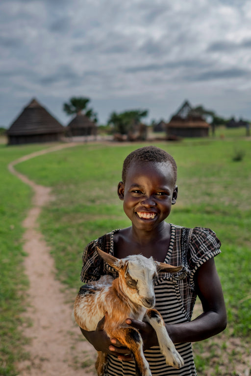Girl holding a goat in front of a village road
