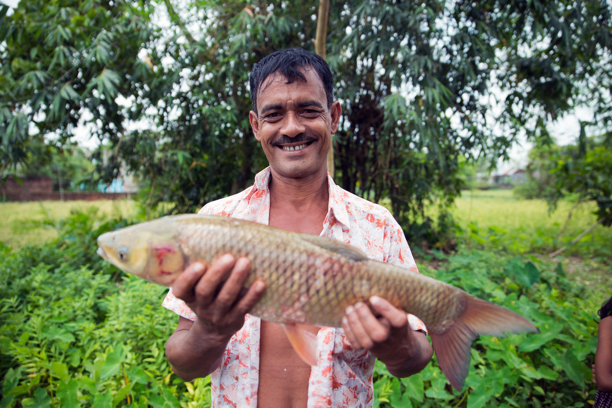 A fisherman holds up a fish.