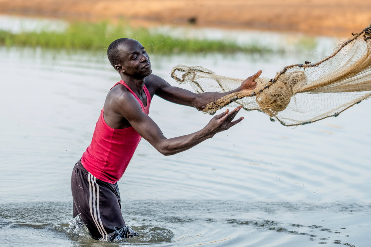 man standing in a pond throwing out a fishing net