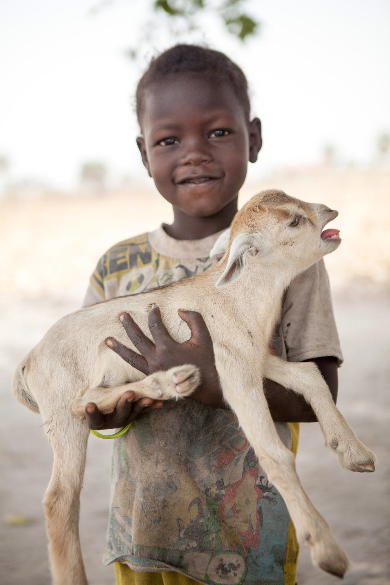 A kid holding his kid goat.