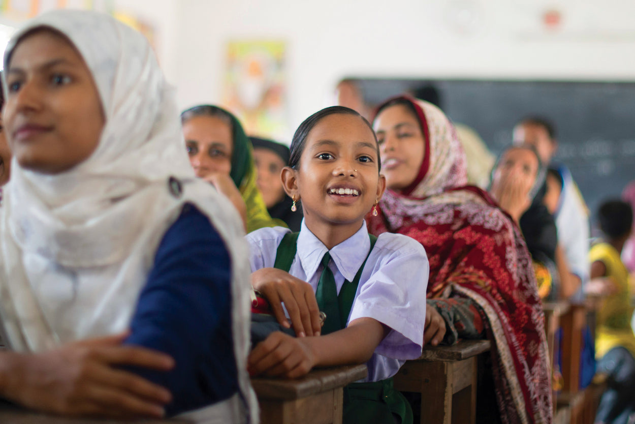 A young girl in Bangladesh sits in class with her peers alert and engaged in learning