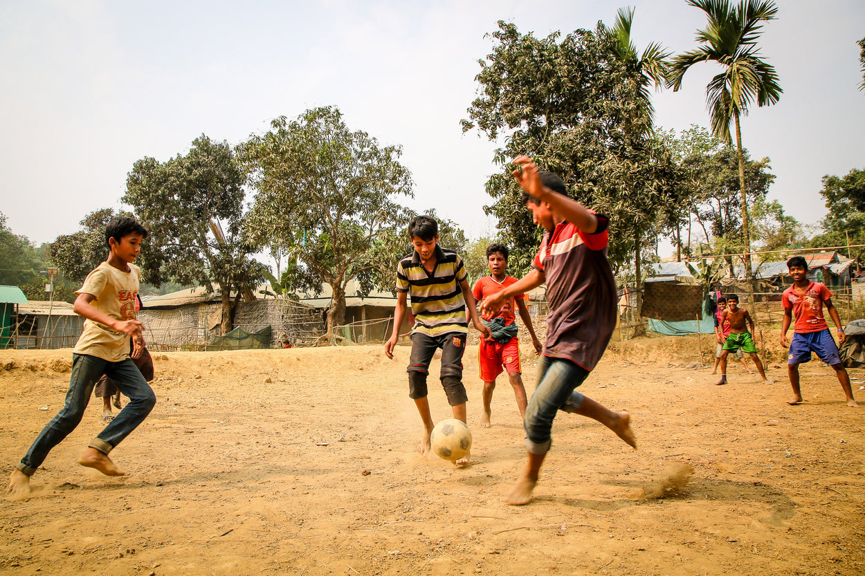 a group of boys playing soccer in the sand