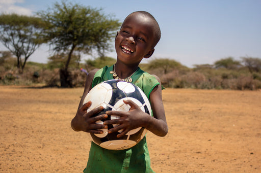 A girl smiles as she holds her soccer ball.