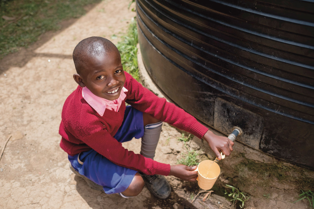 A boy collects clean water from a rainwater collection tank.