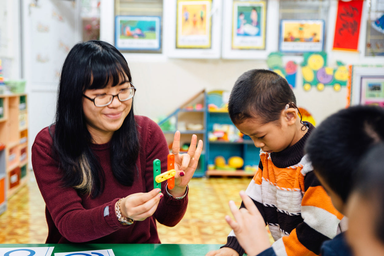 A teacher works with a deaf child teaching the alphabet.