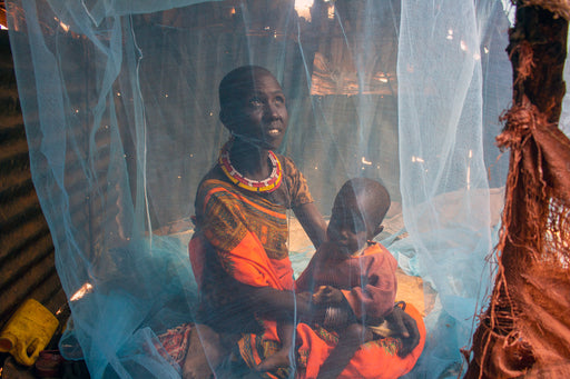 A mother and her baby sit underneath a mosquito net.
