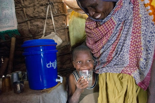 A happy boy drinks clean water from his water filter.