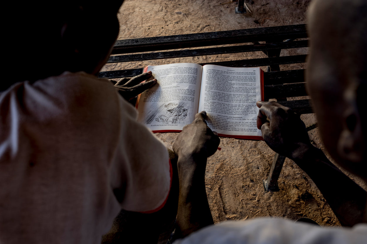two men looking down and reading a Bible