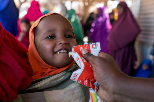 A baby eats an emergency nutrition packet.