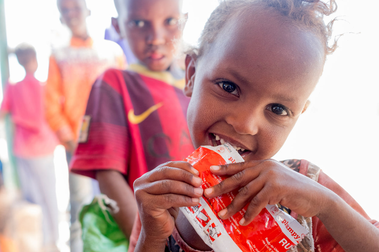 a little girl eating an emergency nutrition packet