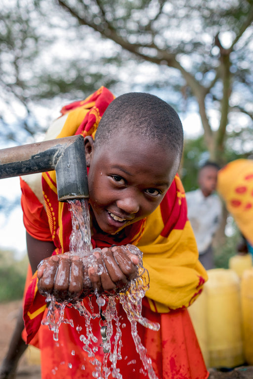 Children smile as they bring up clean water from their village well.