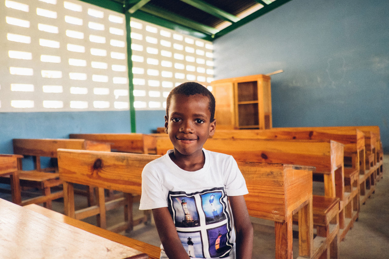 a little boy in a white shirt sitting in an empty classroom