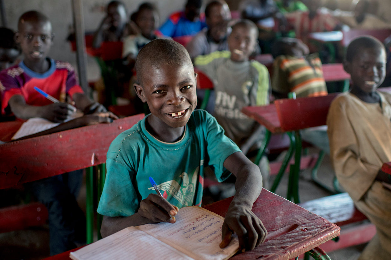 A young boy smiles at his desk because he has a classroom filled with supplies to be able to learn.