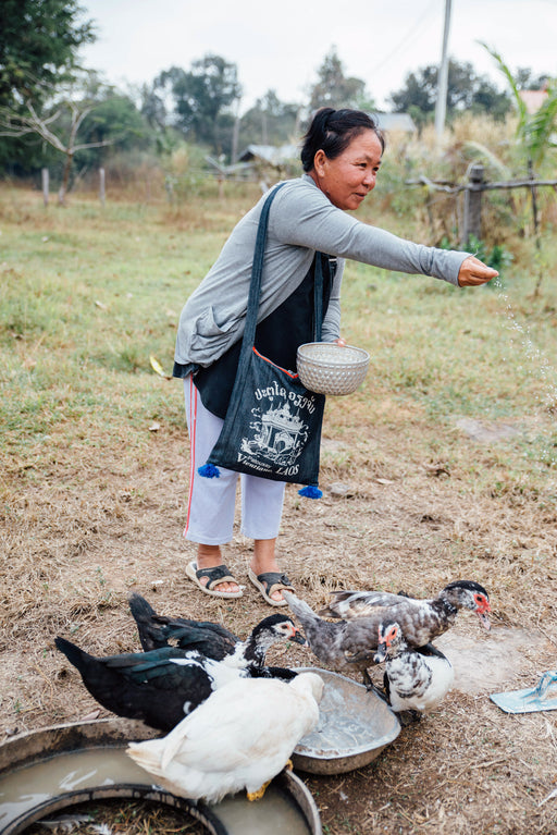 A happy woman feeds her ducks.