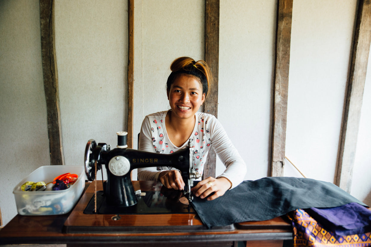 woman sitting behind a sewing machine on a table