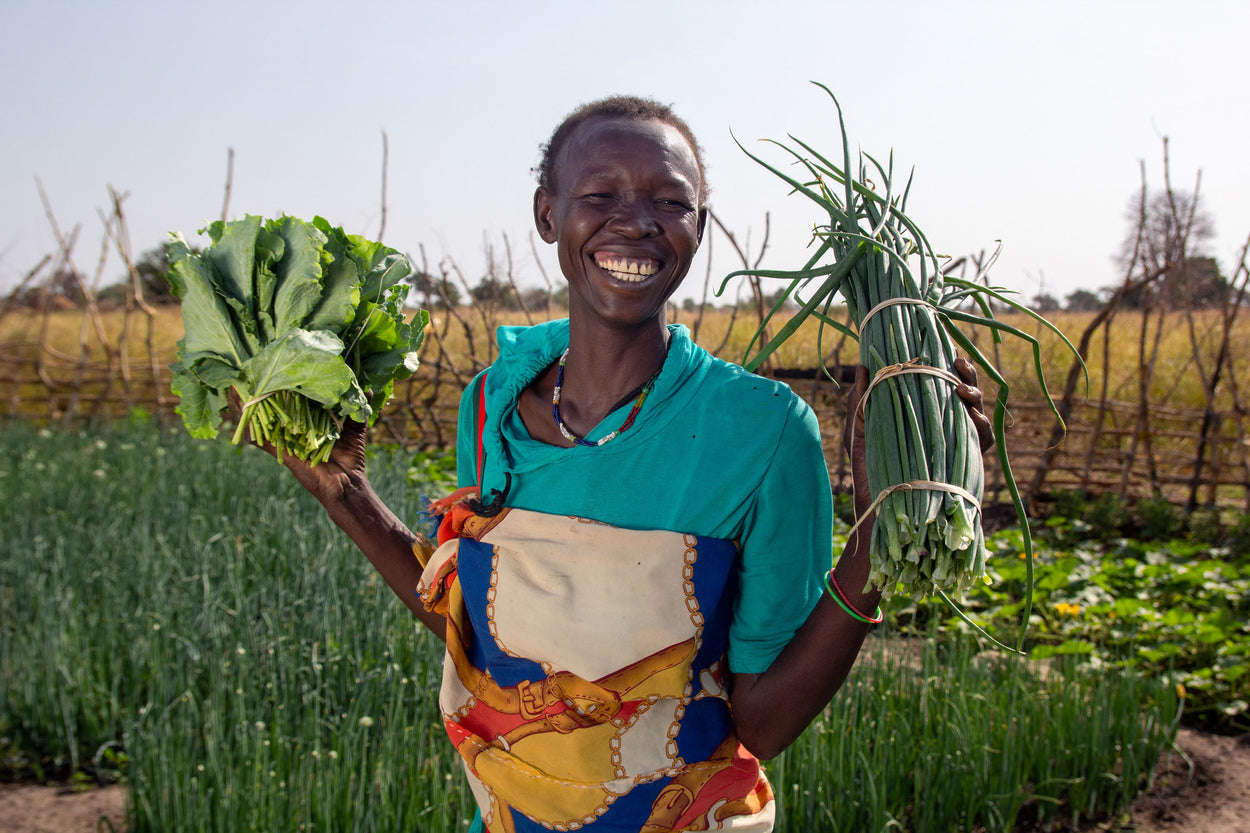 A woman tends to her vegetable garden.