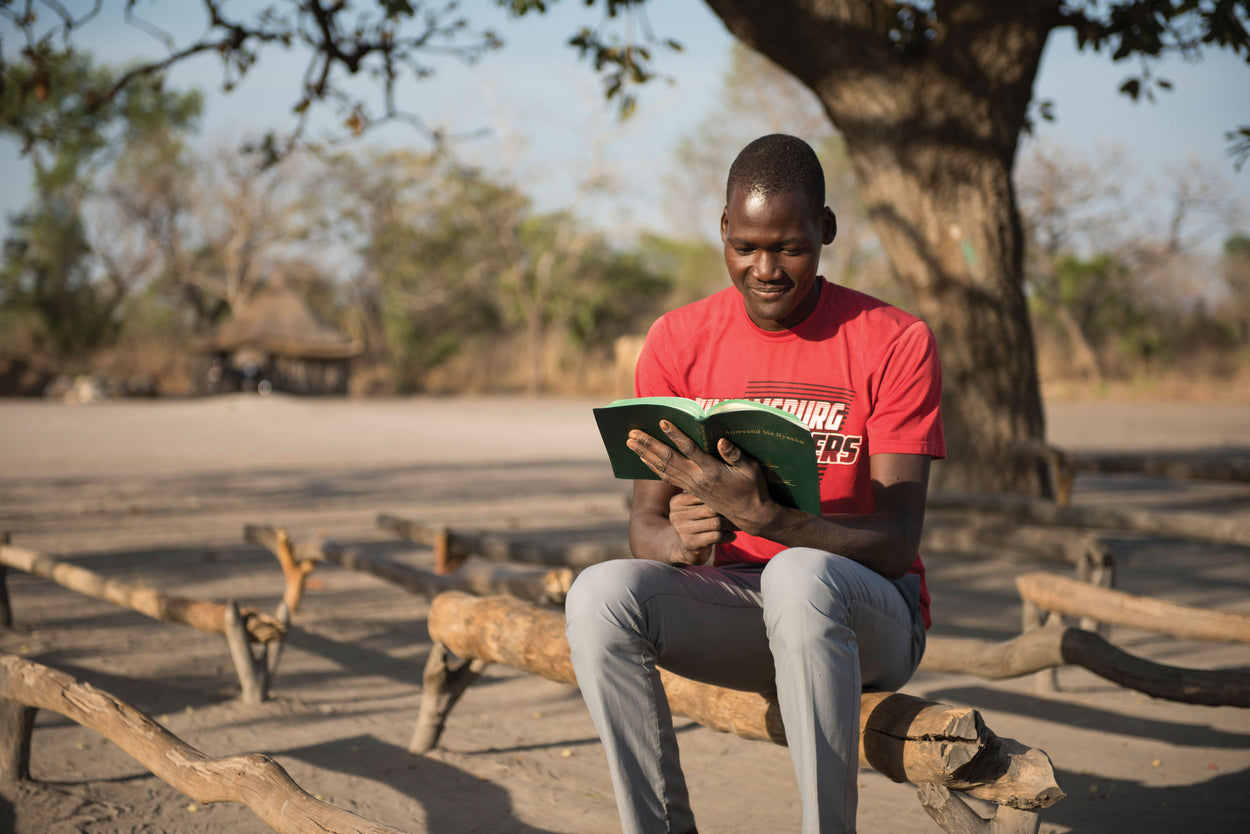A young man reads a bible.