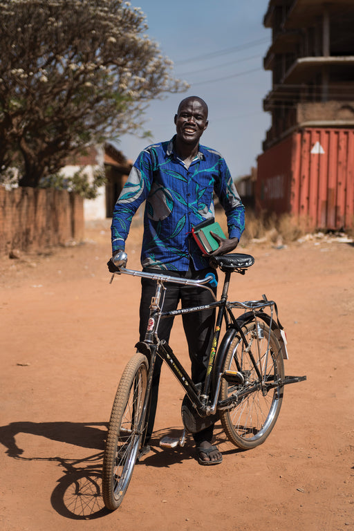 An evangelist stands with his bicycle and a bible.